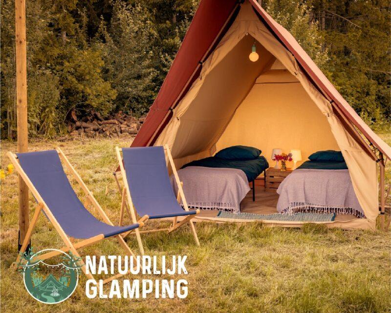 Natuurlijk Glamping tent met twee stoelen ervoor en twee bedden in de tent