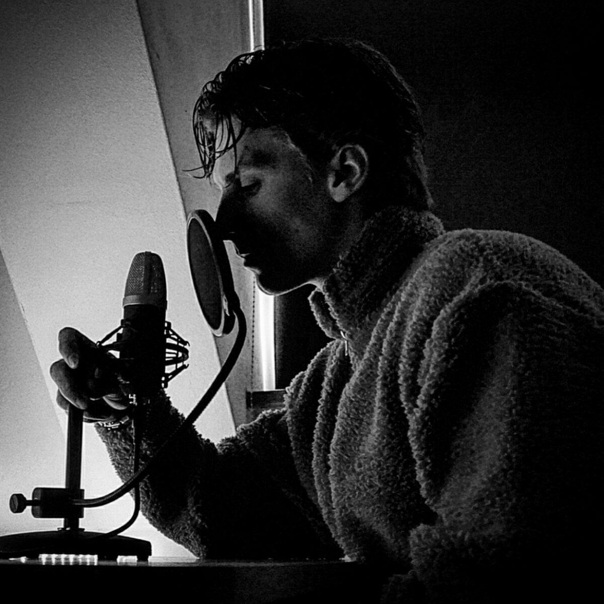 Roger Grizzly spreekt een gedicht in bij een microfoon
