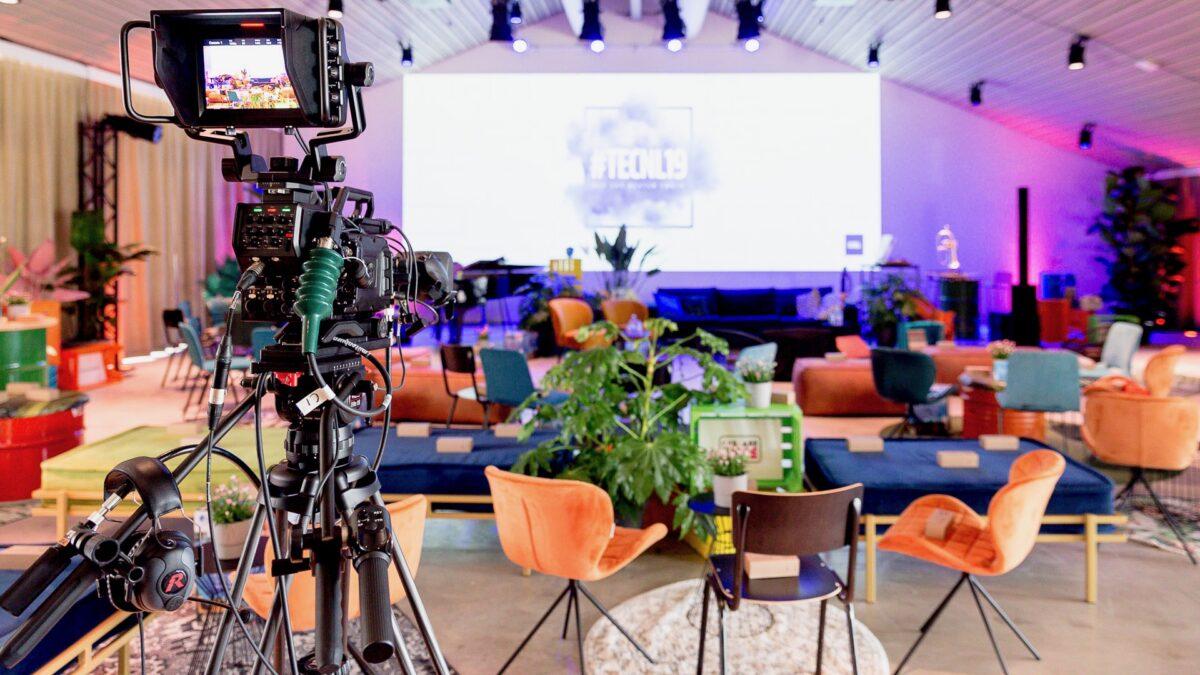 TechNL 19 hybride event met zitjes, podium en camera We Are Live