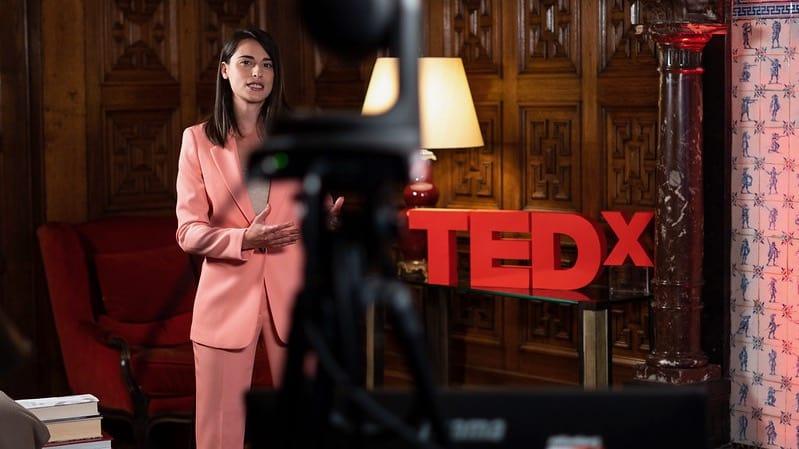 TedX presentatrice naast letters TEDX