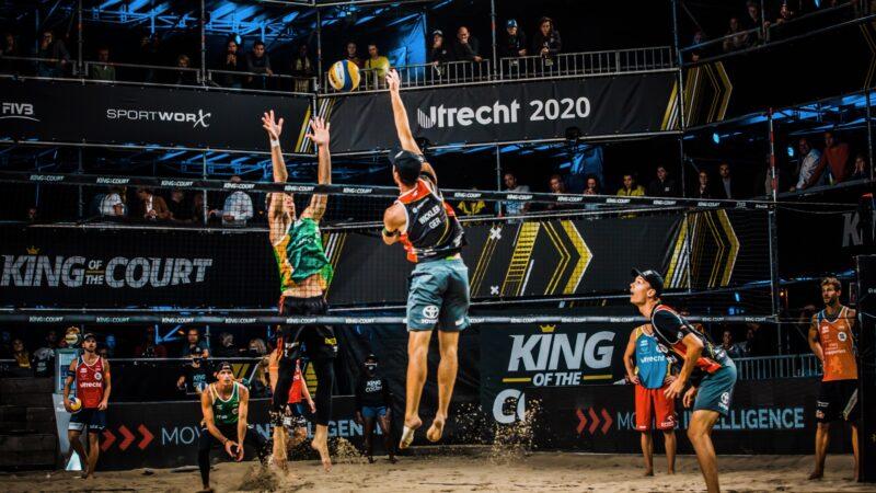Twee beachvolleyballers die omhoog springen bij het net tijdens King of the Court (foto-SetVexy)