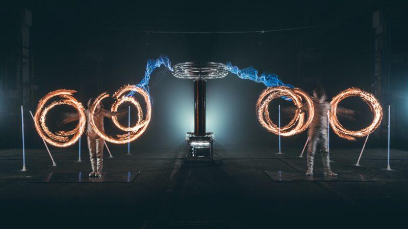 Twee mensen die vuur ronddraaien en electriciteit erachter tijdens Tesla event