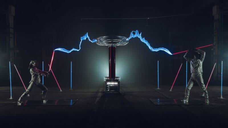 Twee zwaardvechters met lichtgevende zwaarden en electriciteit tijdens Tesla event