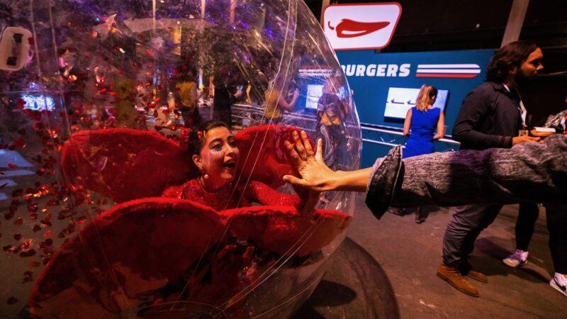 Vrouw in een rode outfit in een opblaasbare bal bij ProjectPlayground_©FlorisHeuer_1092