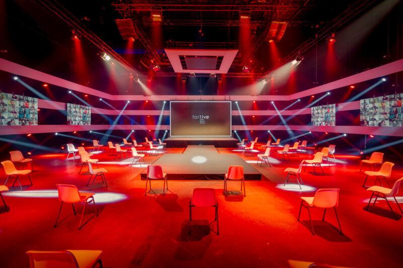Zaal rood uitgelicht met podium bij Central Studios voor hybride events