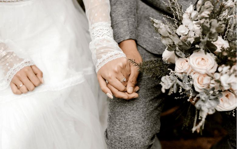 Bruidspaar die elkaars hand vasthoudt - maatregelen corona