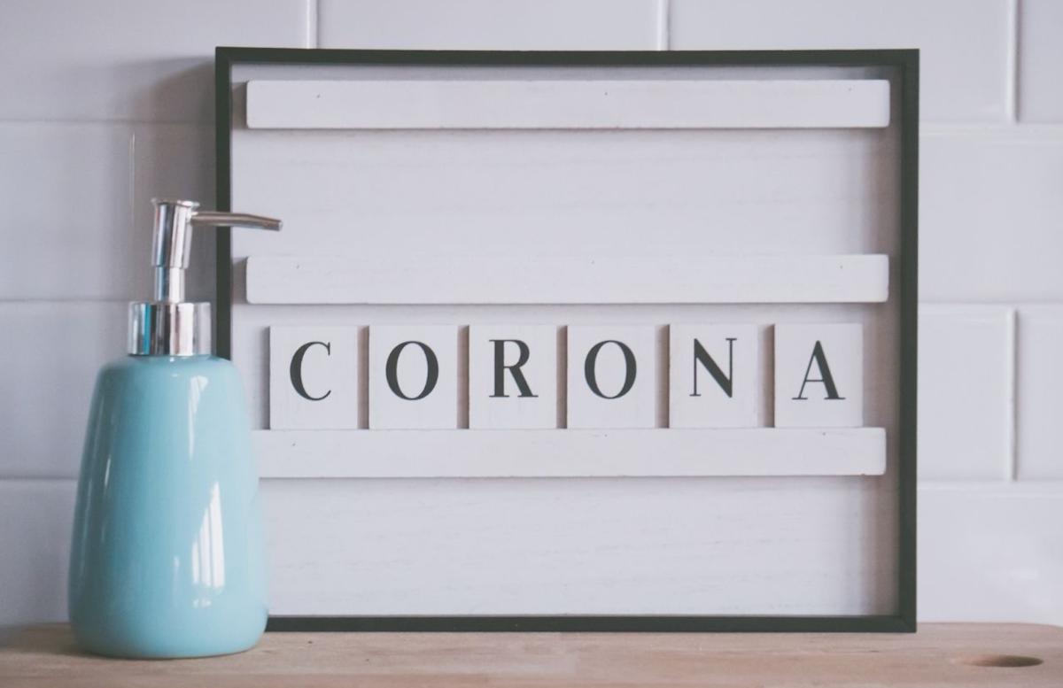 Letterbord met woord corona en een zeeppompje