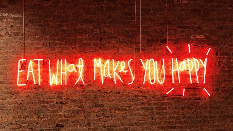 Lichtgevende letters met de zin eat what makes you happy (Foto- Jon Tyson)