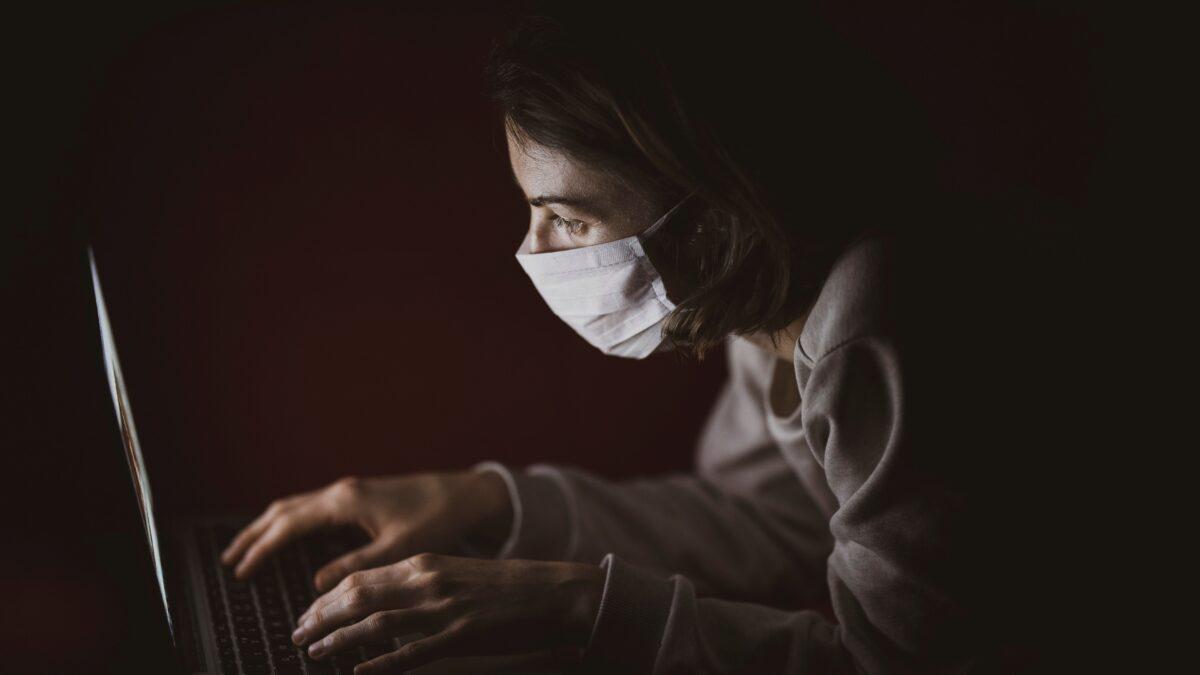 Vrouw met mondkapje achter laptop