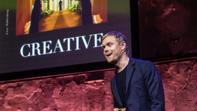 Timo foto van spreker tijdens congres met een presentatie op achtergrond en het woord creative