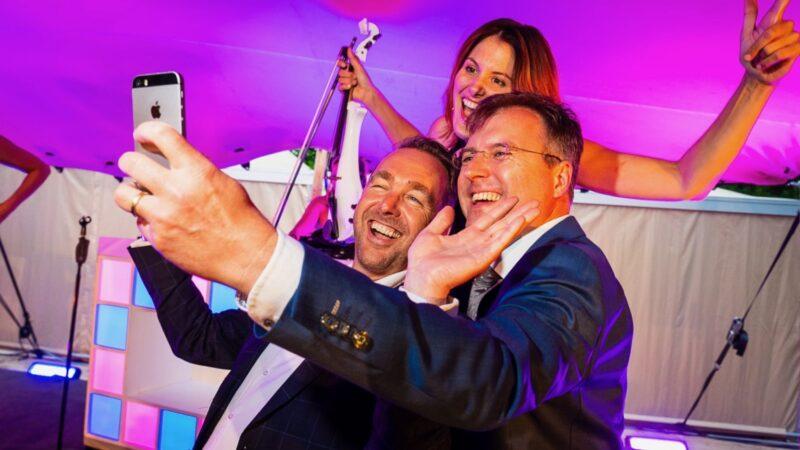 Twee mannen die op de foto gaan met een violist tijdens een feest in een tent - Photo: Tycho's Eye Photography