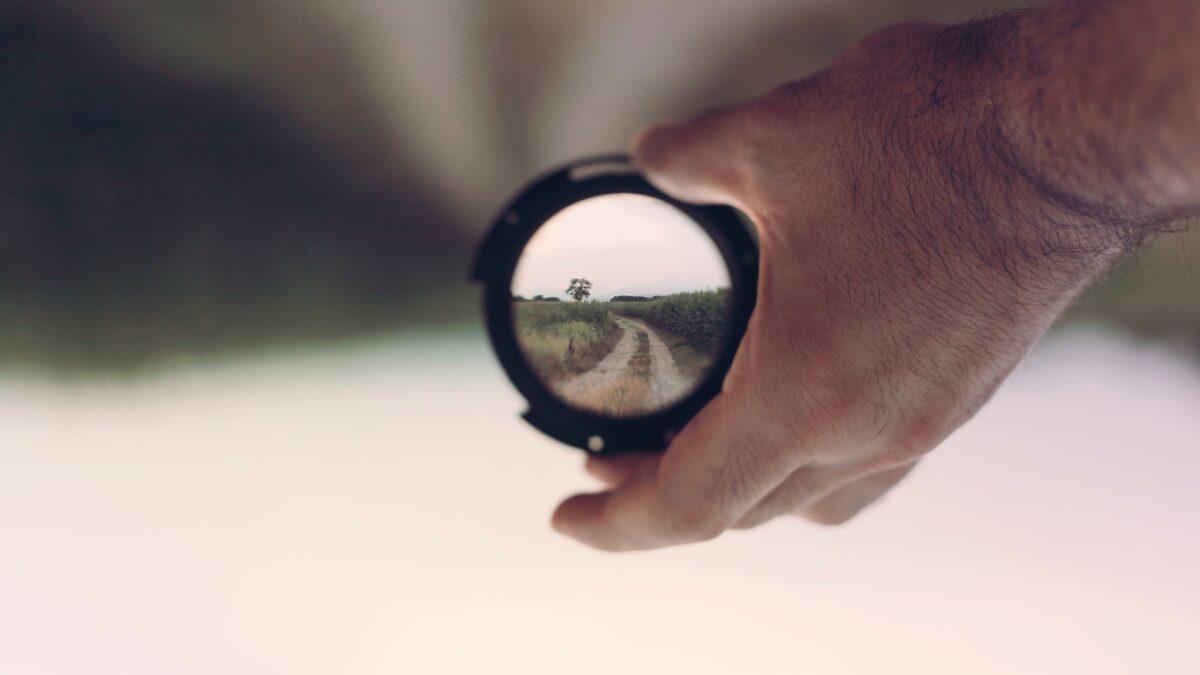 Lens met vergezicht in de hand van een man