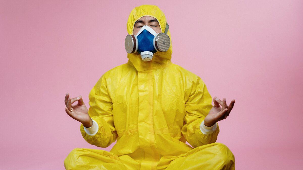 Man in geel coronaproof pak met gasmasker op tijdens corona uitdaging