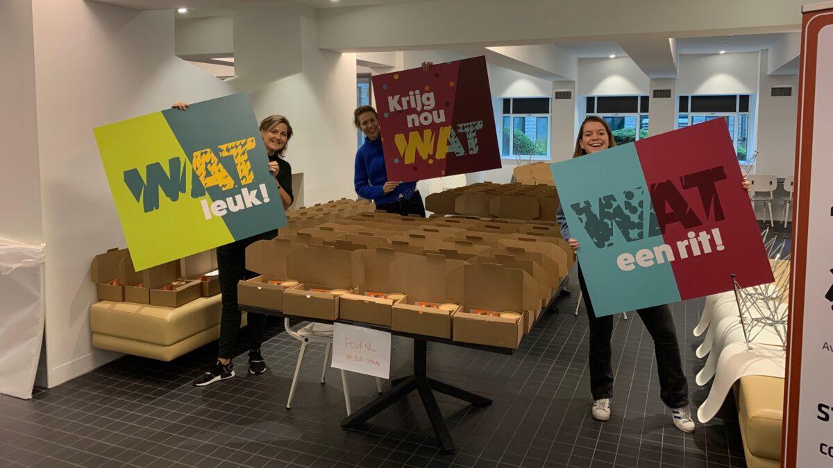 Ingepakte pakketten met 3 medewerkers met borden met teksten wat leuk, krijg nou wat en wat een rit