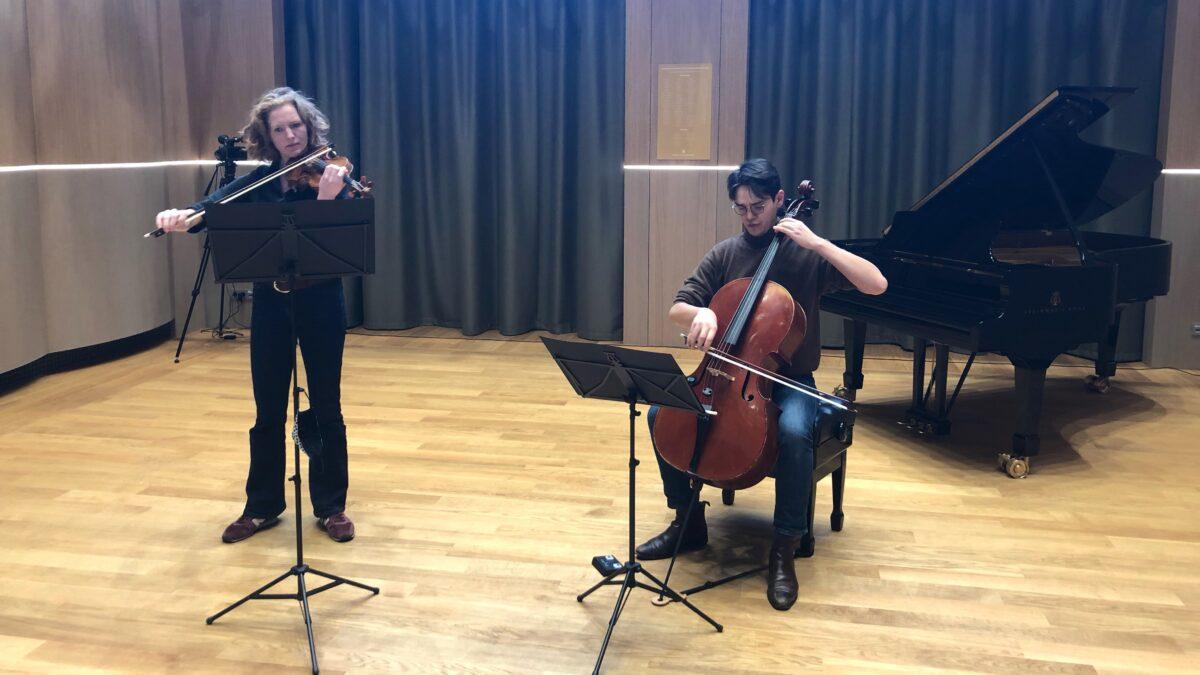 Optreden violist en cellist met piano op de achtergrond