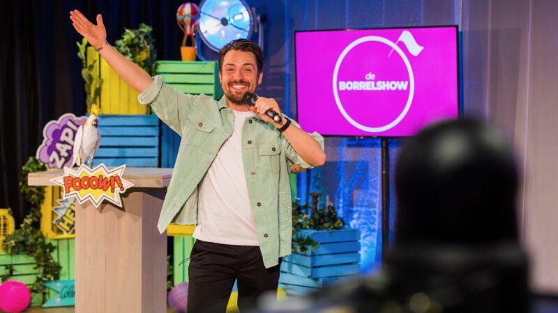 Presentator-tijdens-de-borrelshow-met-roze-scherm-achter-zich (Foto: Twycer)