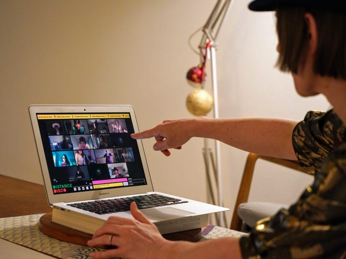 Distance Disco man achter laptop met op het scherm dansende mensen voor de webcam