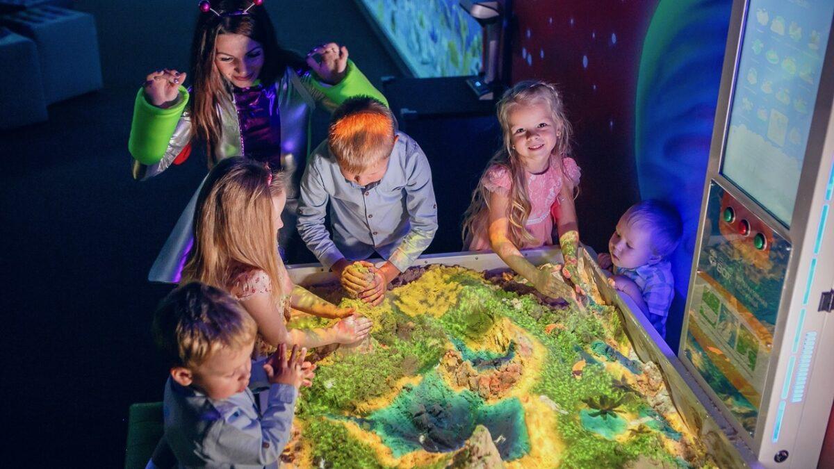 Kinderen die spelen met een interactieve zandbak met projecties