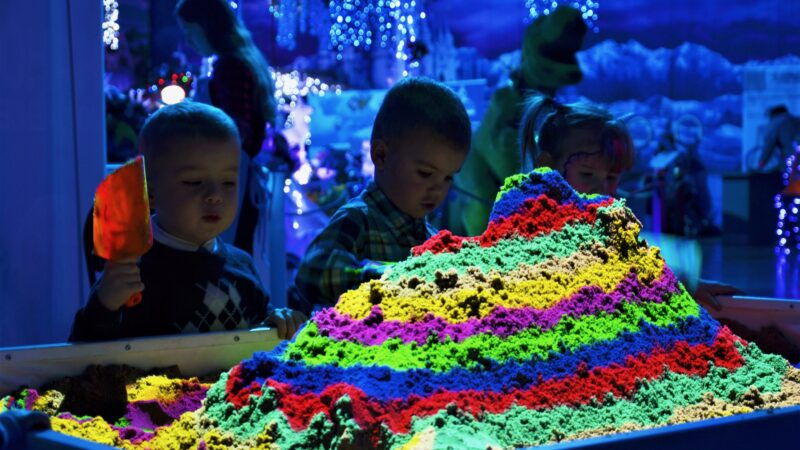 Kinderen die spelen met interactieve zandbank in regenboogkleuren