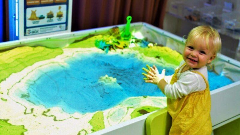 Klein kind bij interactieve zandtafel met projectie