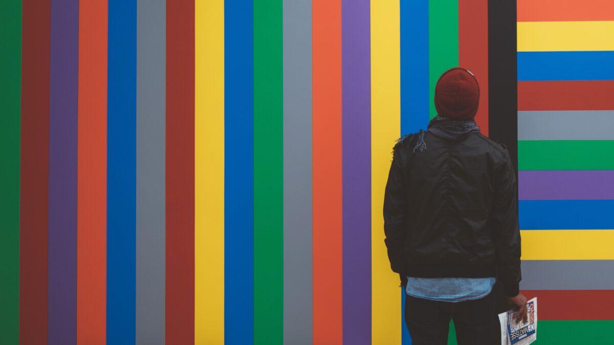 Man die staat voor een muur met gekleurde strepen - diversiteit