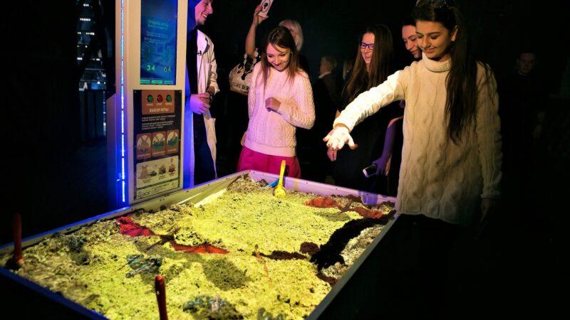 Mensen die spelen met schaduwen op interactieve zandbak met projecties