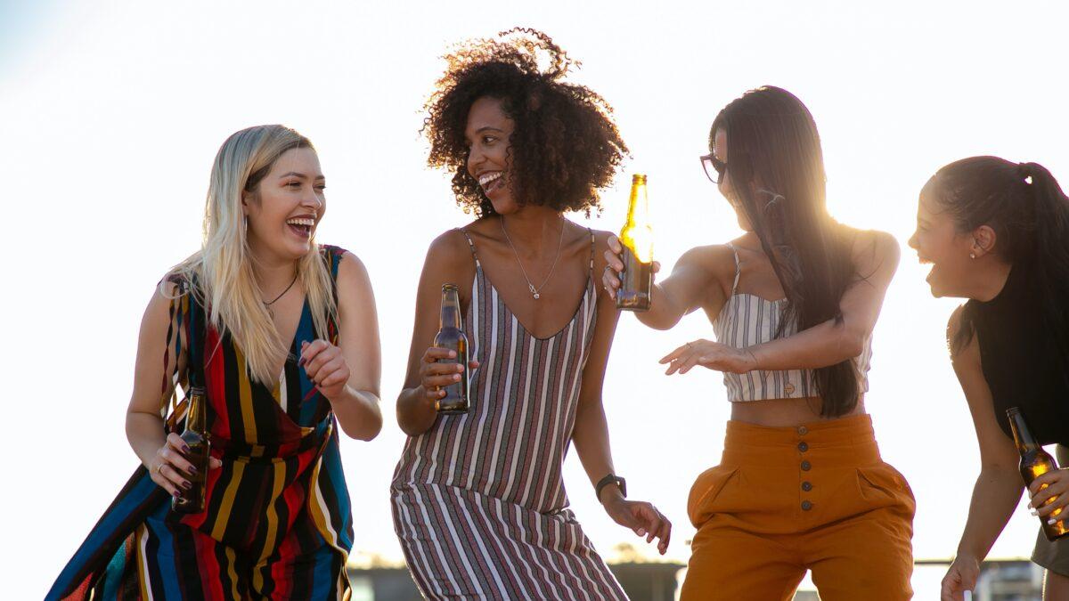 Proost Corona Party vier vrouwen die aan het dansen zijn met een flesje bier in hun hand (Foto-Tycho