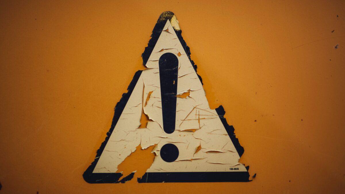 Verkeersbord met uitroepteken met afgebladderde verf