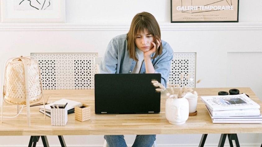 Vrouw die zich verveelt achter een laptop