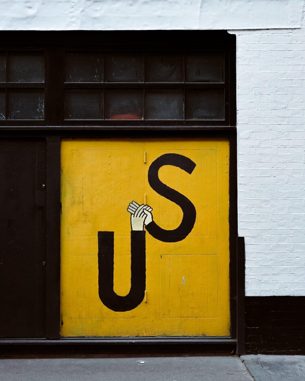 Woord US met handjes geschilderd op een gele deur