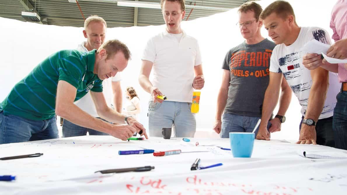 Het nieuwe werken op kantoor brainstorm met groepje mannen bij wit vel met stiften (foto - Tychos Eye)