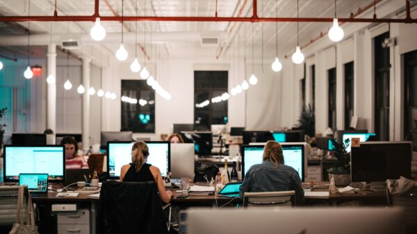 Mensen die op kantoor aan het werk zijn met rijen bureaus naast elkaar