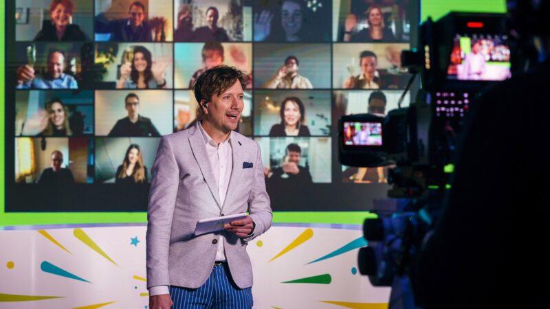 Presentator-Klaas-met-zoom-scherm-achter-zich-tijdens-online-event-Baker-Tilly-foto-Tychos-Eye-Photography