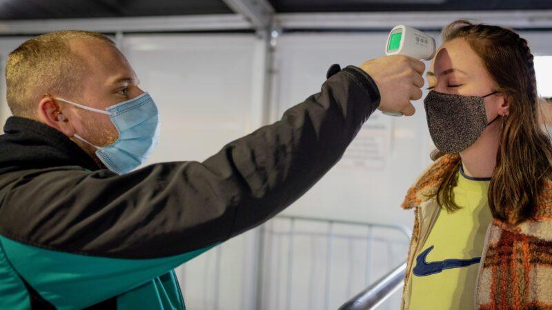 Resultaten Fieldlab testevent vrouw wiens temperatuur wordt gemeten door beveiliger