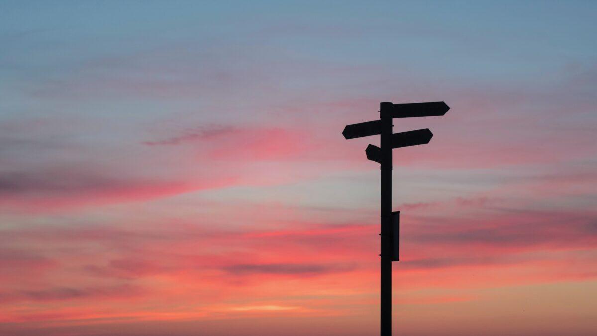 wegwijsbordjes in zwart met een zonsondergang op de achtergrond