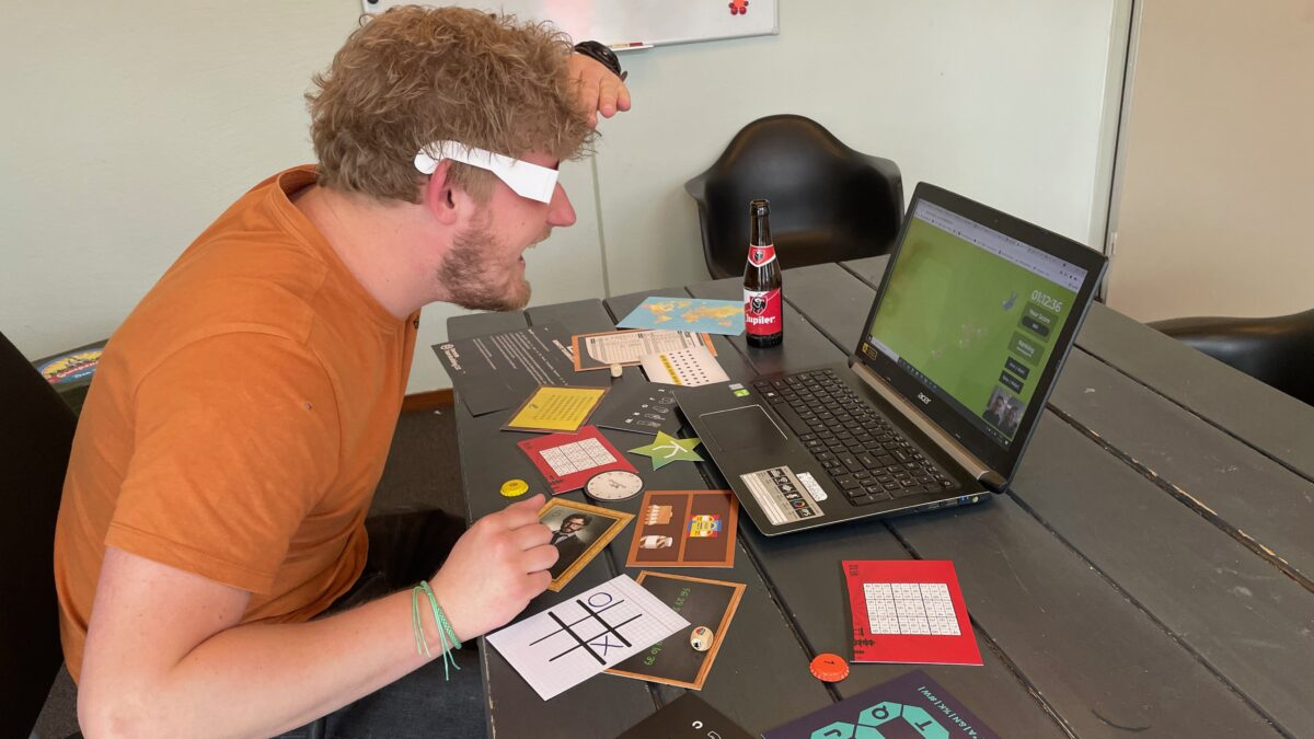 Remote Teambuilding The Box Company - man achter laptop met opgaven
