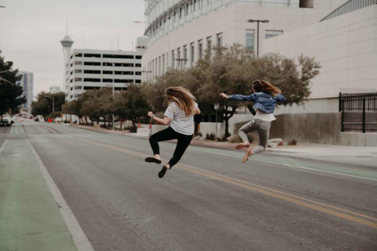 Twee vrouwen die in de lucht springen van blijdschap
