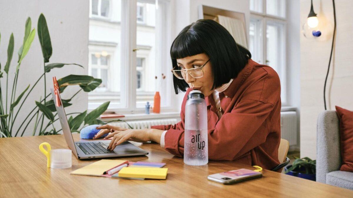 Vrouw achter laptop die aan het drinken is uit een waterfles van air up