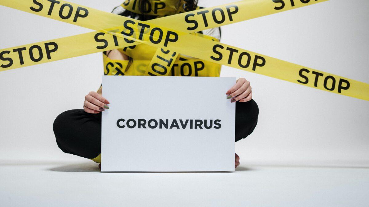 Vrouw ingepakt met geel tape met stop erop en een bord met coronavirus