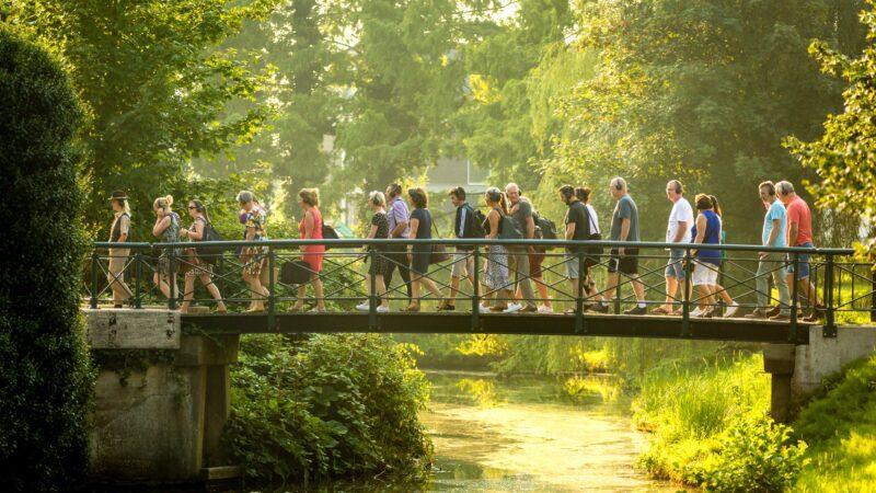 Buro Curious - mensen die op een brug door een park lopen met een koptelefoon op