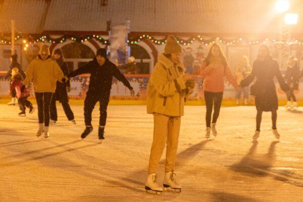 Mensen aan het schaatsen op een verlichte ijsbaan